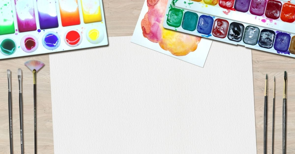 photo of watercolour paints, brushes and paper
