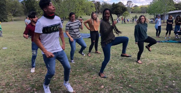 Young people teach each other cultural dances at a You Belong Welcome Party.
