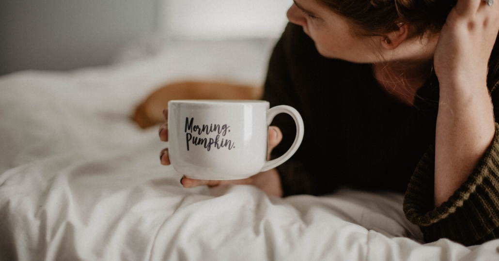 """woman lying on bed with mug that has """"morning pumpkin"""" on it"""