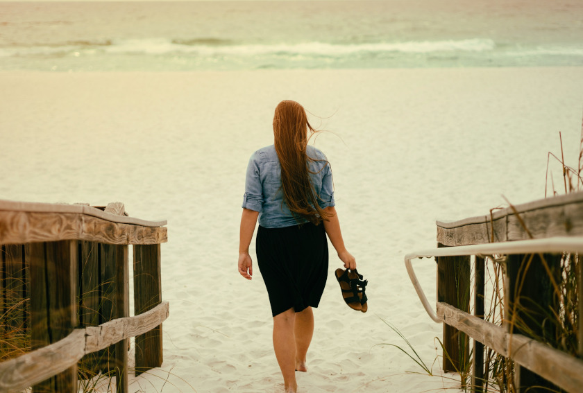 Woman walking toward the ocean barefoot