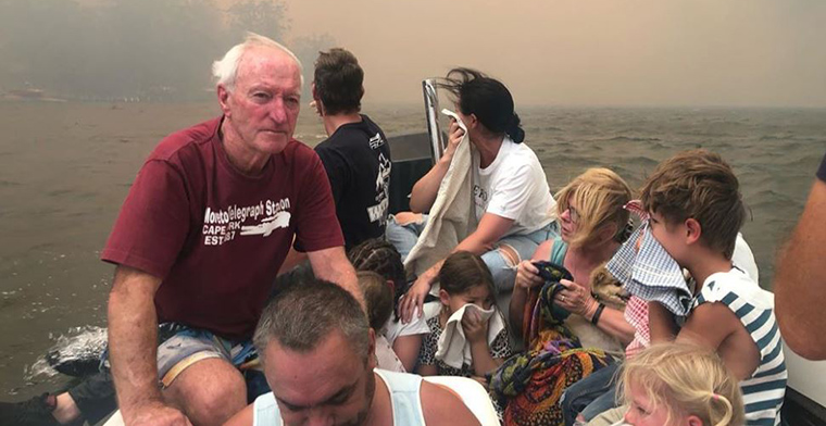 Boat filled with people on lake with fire raging behind them