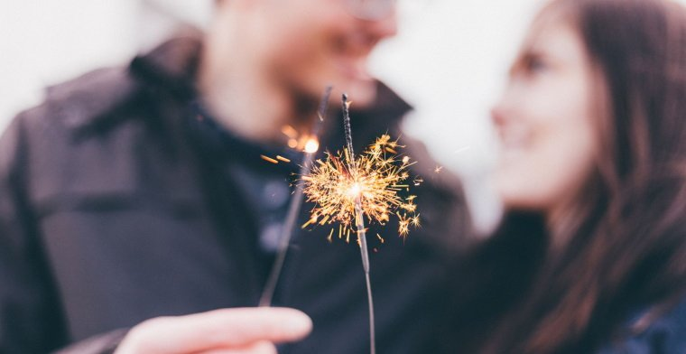 Blurred image of couple with sparklers in forground