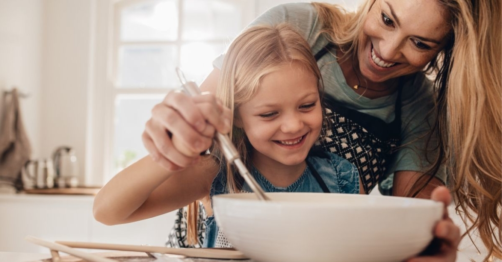 photo of a happy mum and daughter stirring a baking bowl