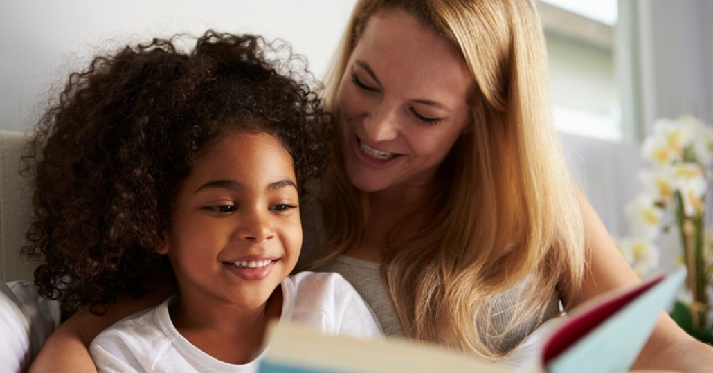 photo of a mother and daughter reading a book together