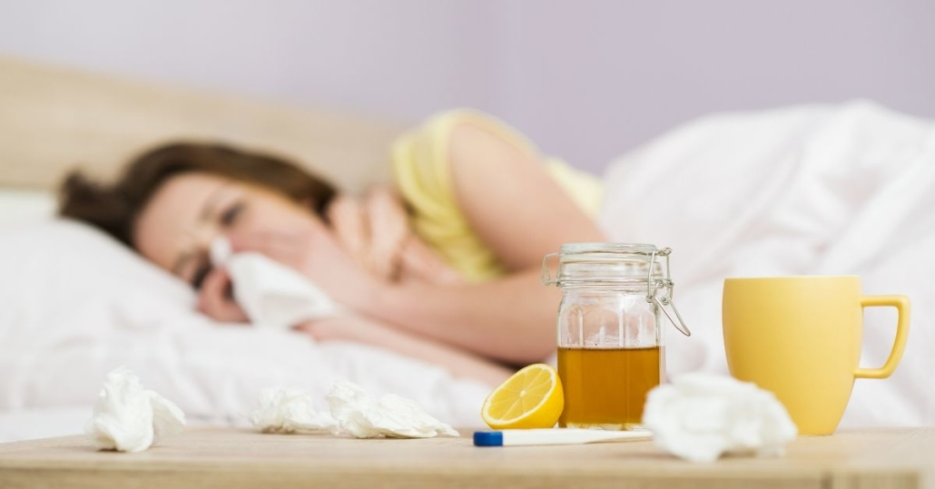 photo of a sick woman laying in bed blowing her nose