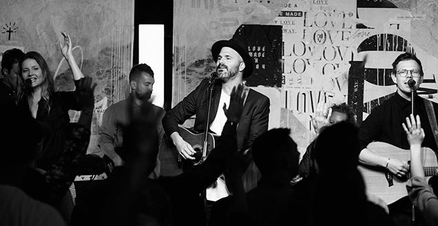 Greg (centre) leads worship in Sydney.