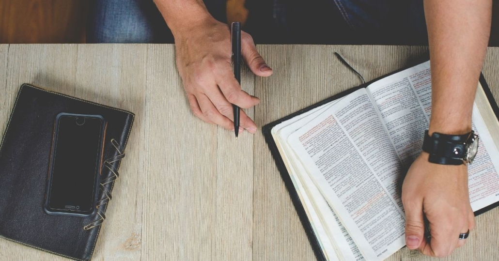 photo of a man reading a bible at a table with pen