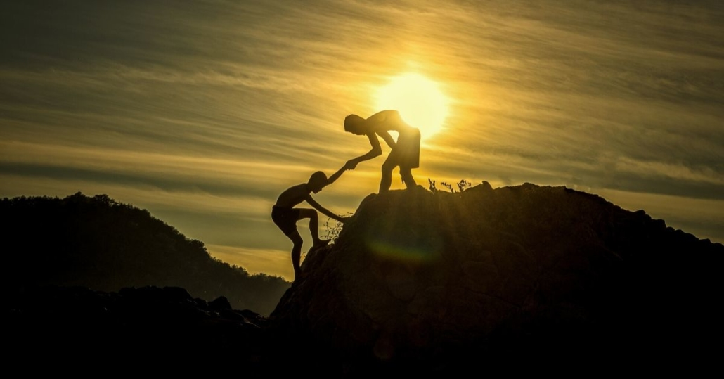 photo of a man helping another man up a mountain