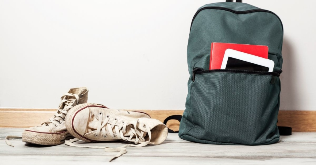 photo of a school bag and converse branded shoes against a white wall