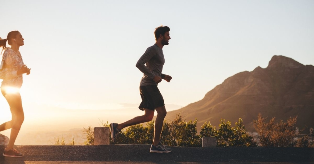 photo of a man and woman running at sunrise