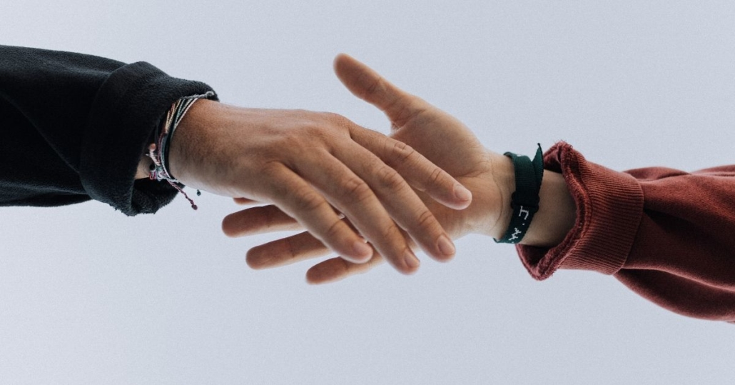 close up photo of a hand reaching for another hand