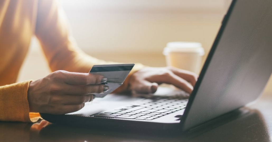 photo of a woman's hand holding a credit card as she sits at her laptop. Online shopping may increase after COVID-19