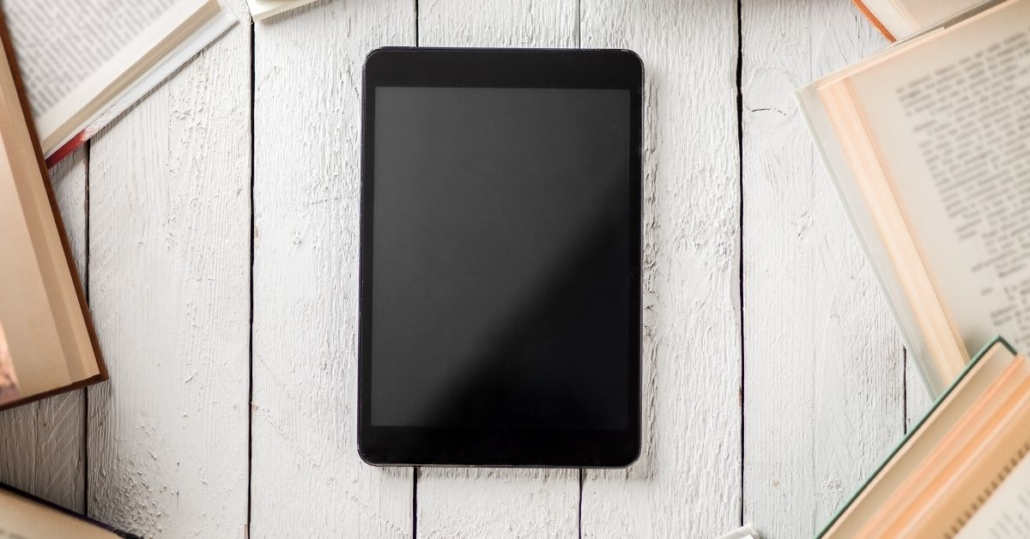 photo of a tablet surrounded by books, maybe the new format of books after COVID-19