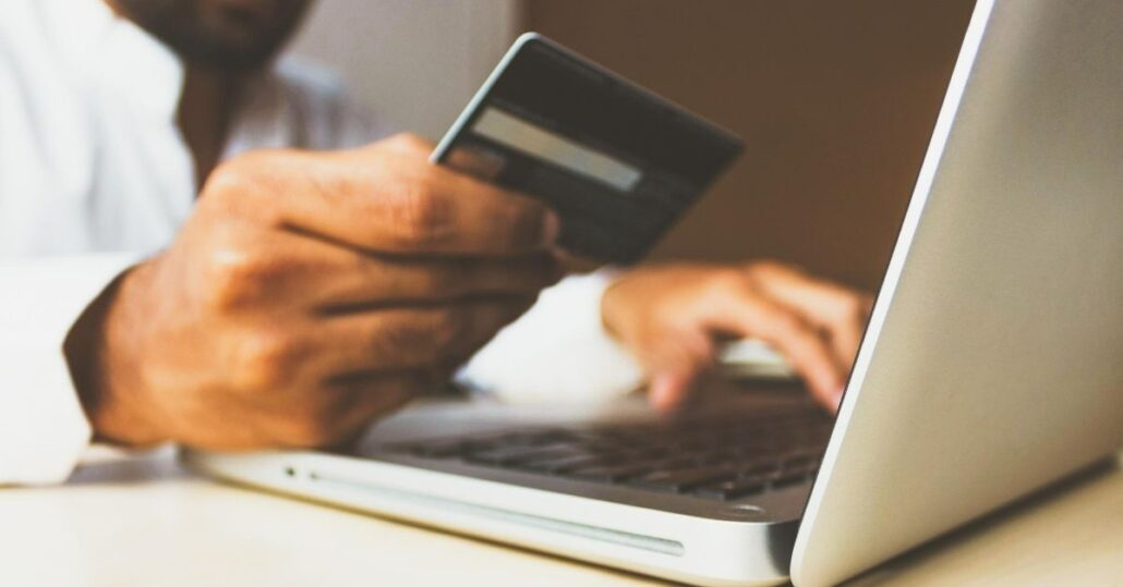 person holding credit card at computer